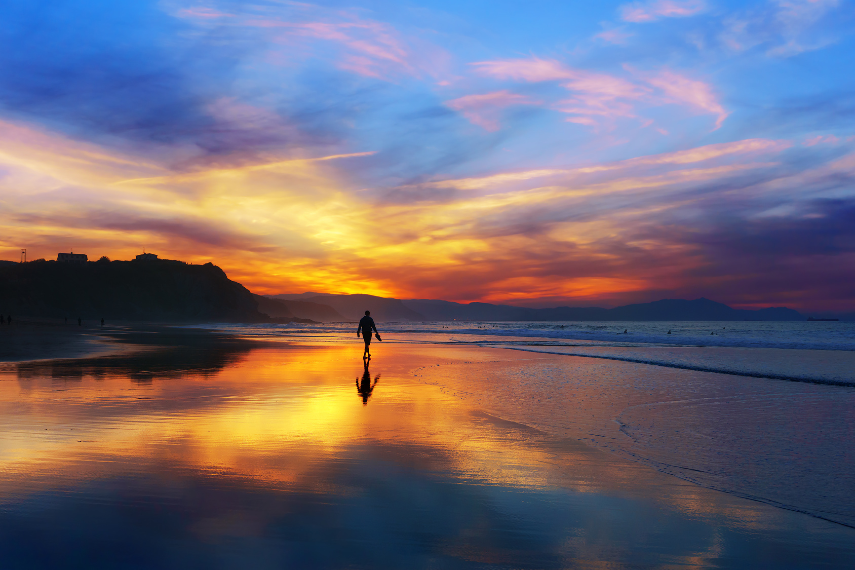 man walking on the beach at the sunset